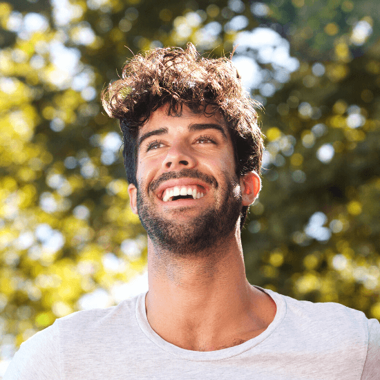 Man with perfect teeth smiling outside.